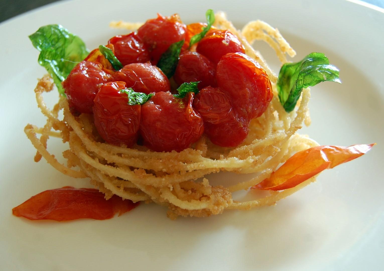 Nido di spaghetti fritti con pomodoro e basilico fritti