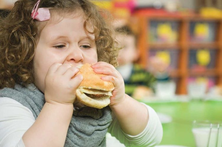 Bambina sovrappeso mangia hamburger