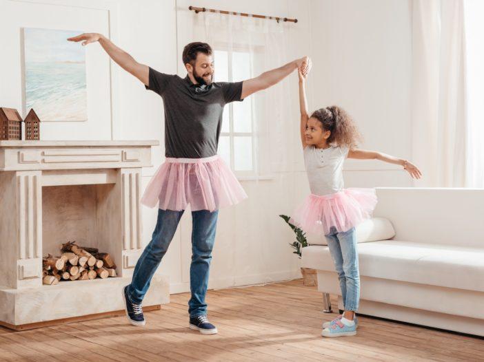 padre e figlia fanno ginnastica in casa ballando